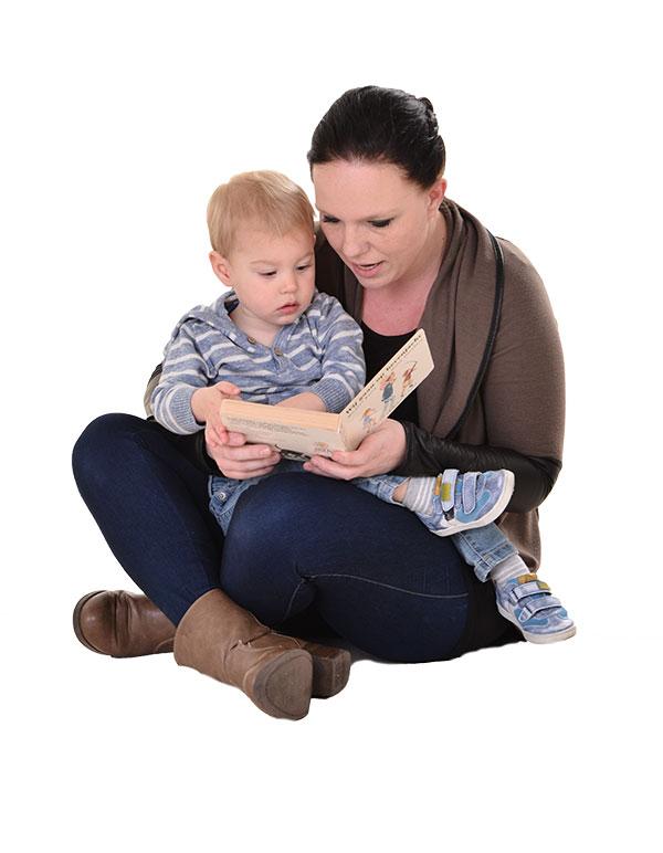 Tarieven kinderopvang Nannies Kinderdagverblijven - leidster en kind lezen samen een boek